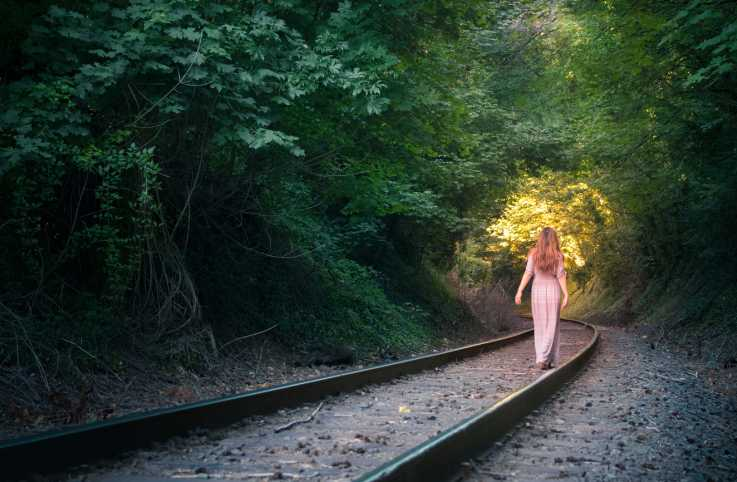 A woman walking on abandoned railroad tracks towards a mysterious glowing light.