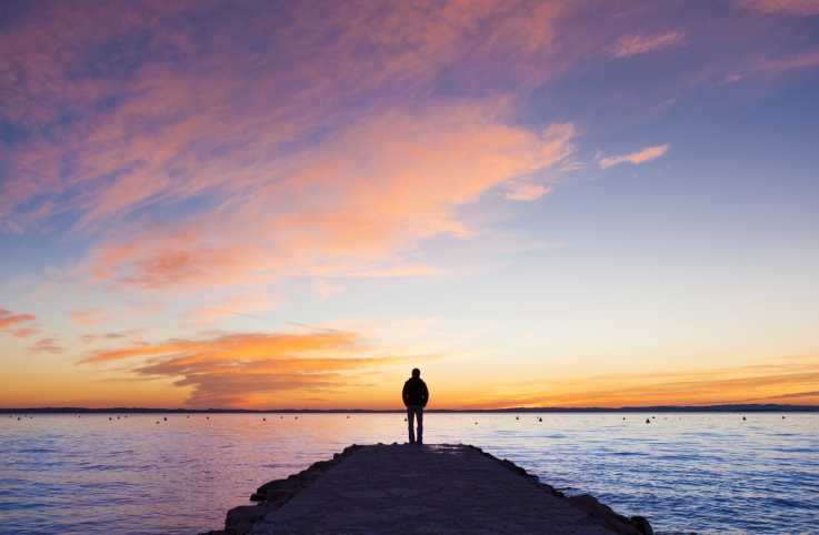 A silhouette of a man in contemplation on a jetty as the sun sets.