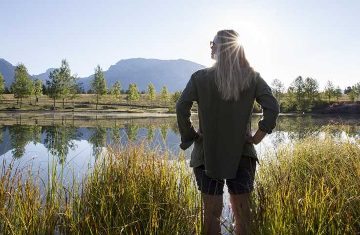 Woman with hands on hips at a mountain lake.