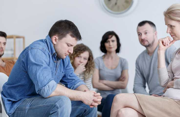 A young man struggles during a recovery support group session