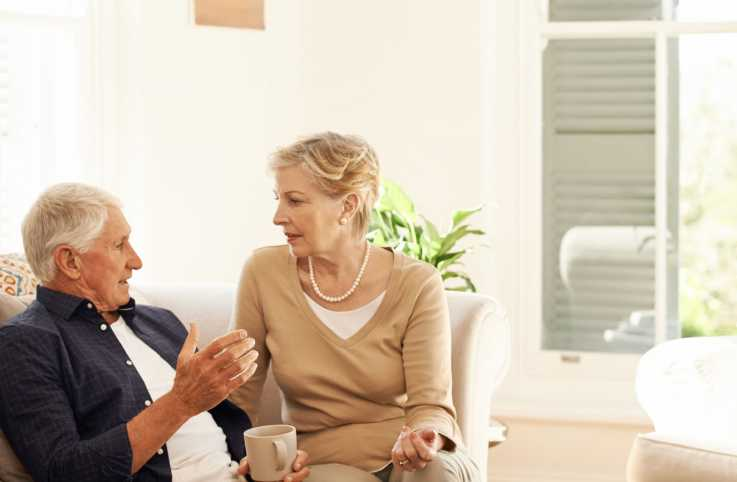 A senior couple having a chat and coffee break on their sofa at home.