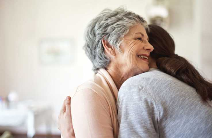 A caregiver daughter hugging her elderly mother.