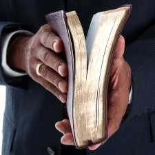 A Bible rests in a pastor's hands