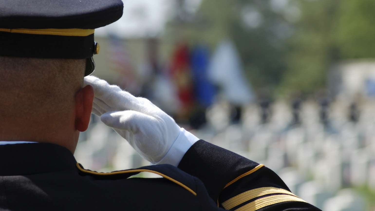 Soldier salutes fallen soldiers in a cemetery on Memorial Day