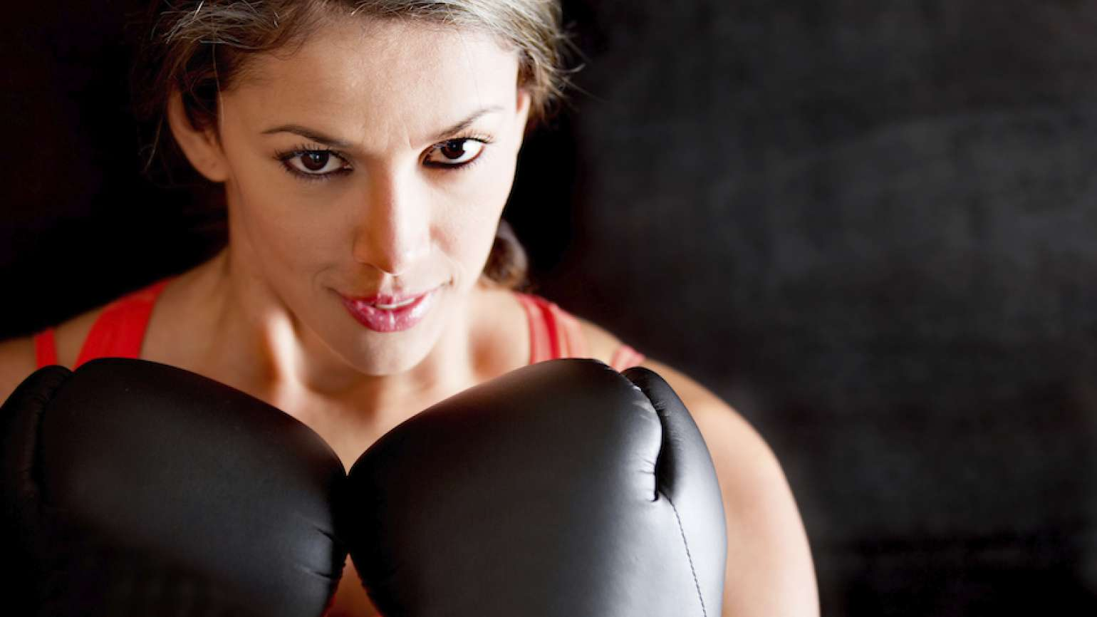 Woman wearing boxing gloves. Thinkstock.