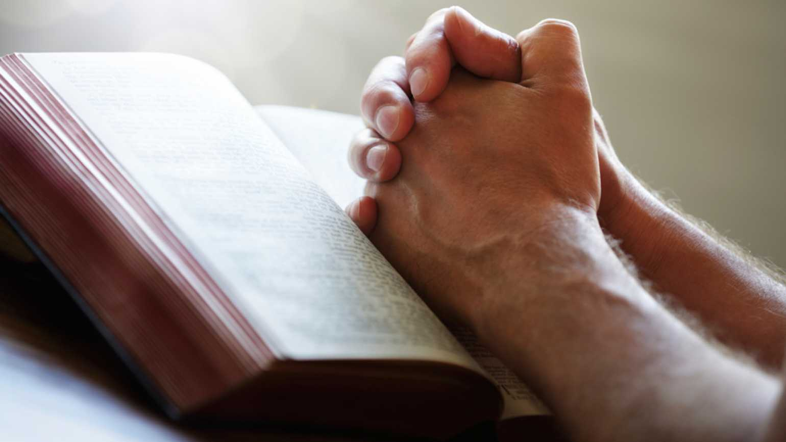 Guideposts: A man's hands, clasped in prayer, rest on the pages of an open Bible