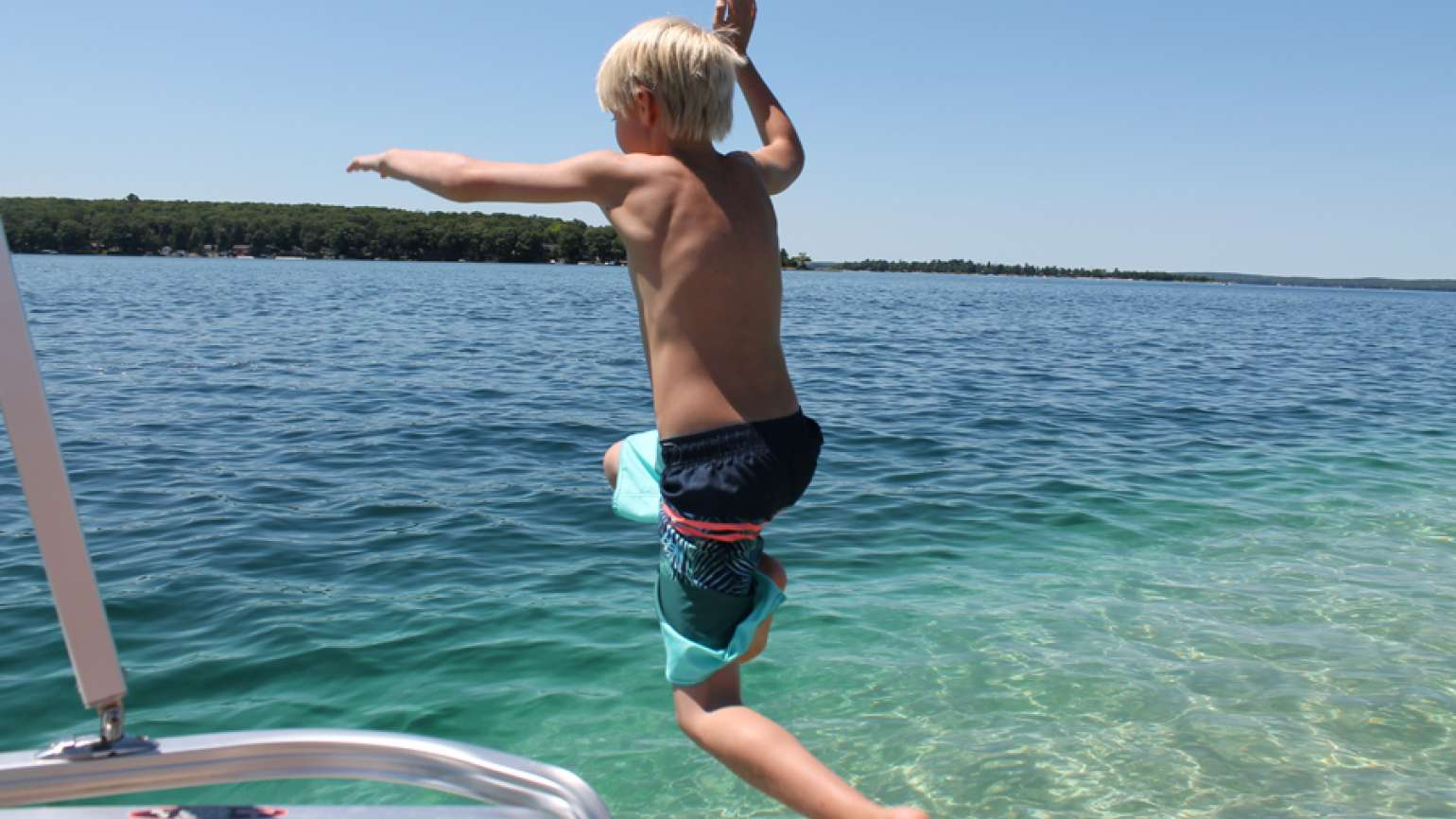 Shawnelle's son jumping off the boat into the lake in Michigan