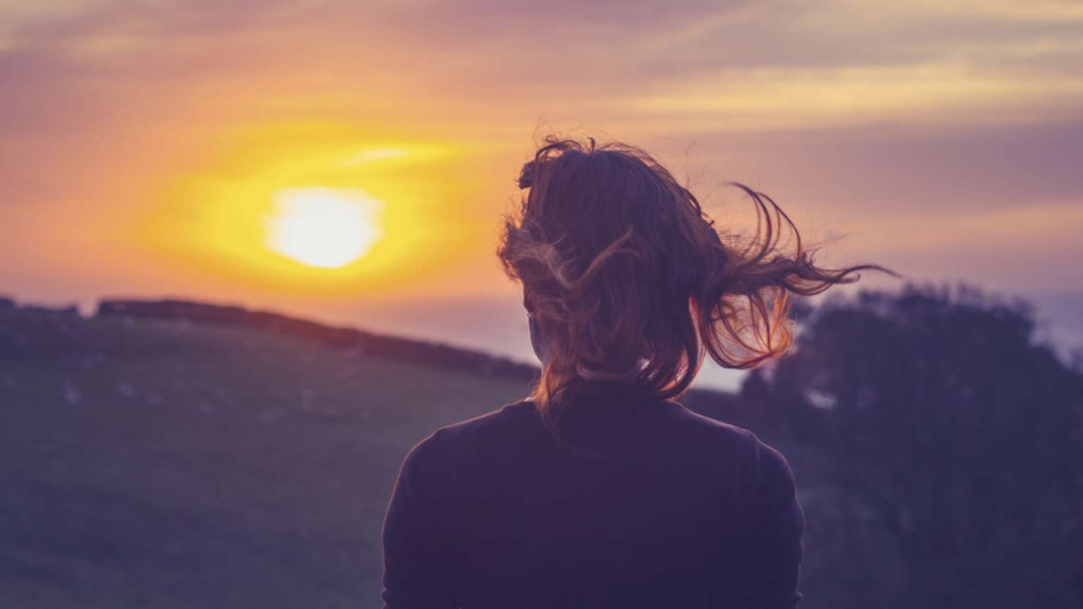 Woman looking at the sunset with wonder