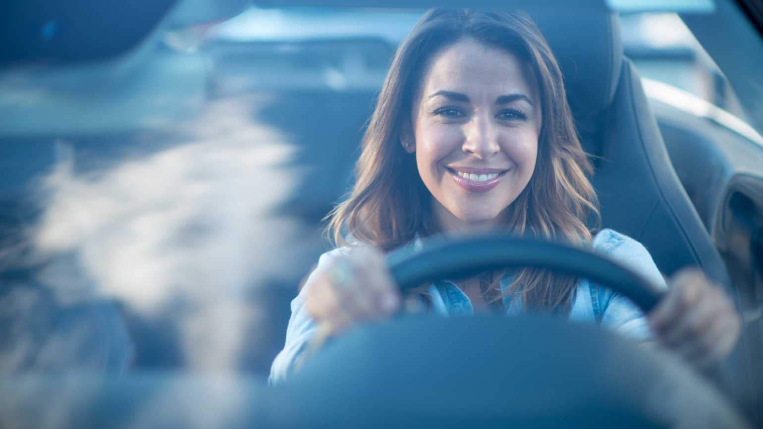 A smiling woman at the wheel of her car