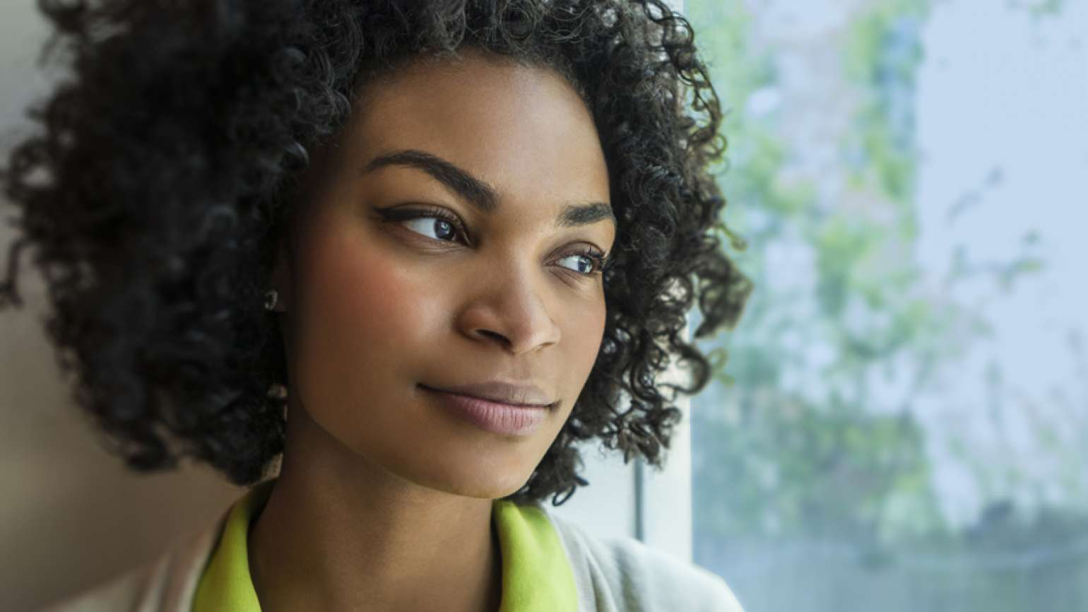 Guideposts: A woman gazes thoughtful out a window.