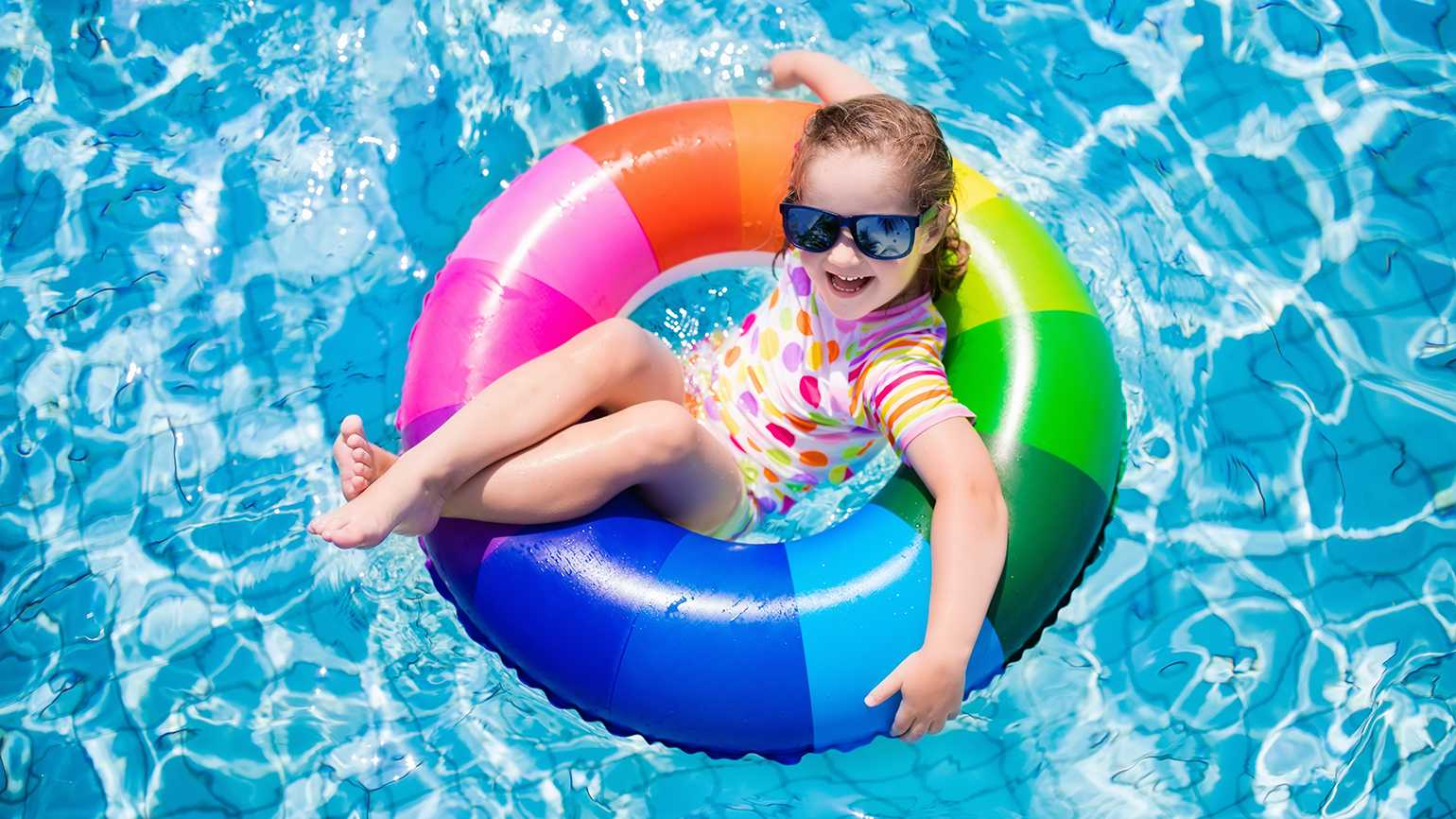 A young girl lounges on a float in a swimming pool