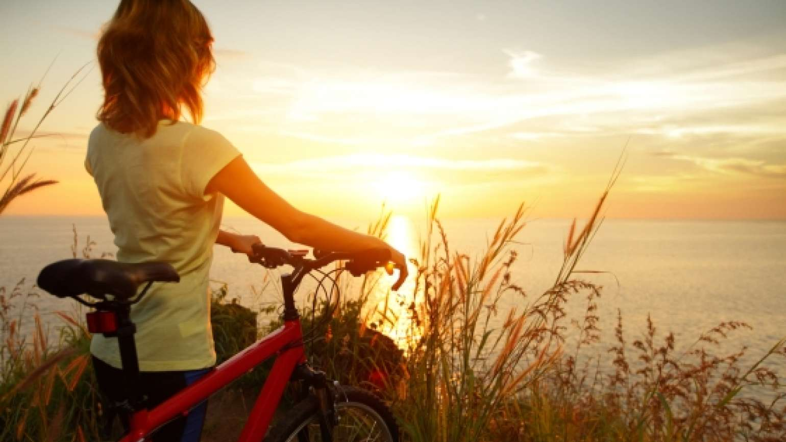 woman on bicycle thoughtfully taking in the sunrise