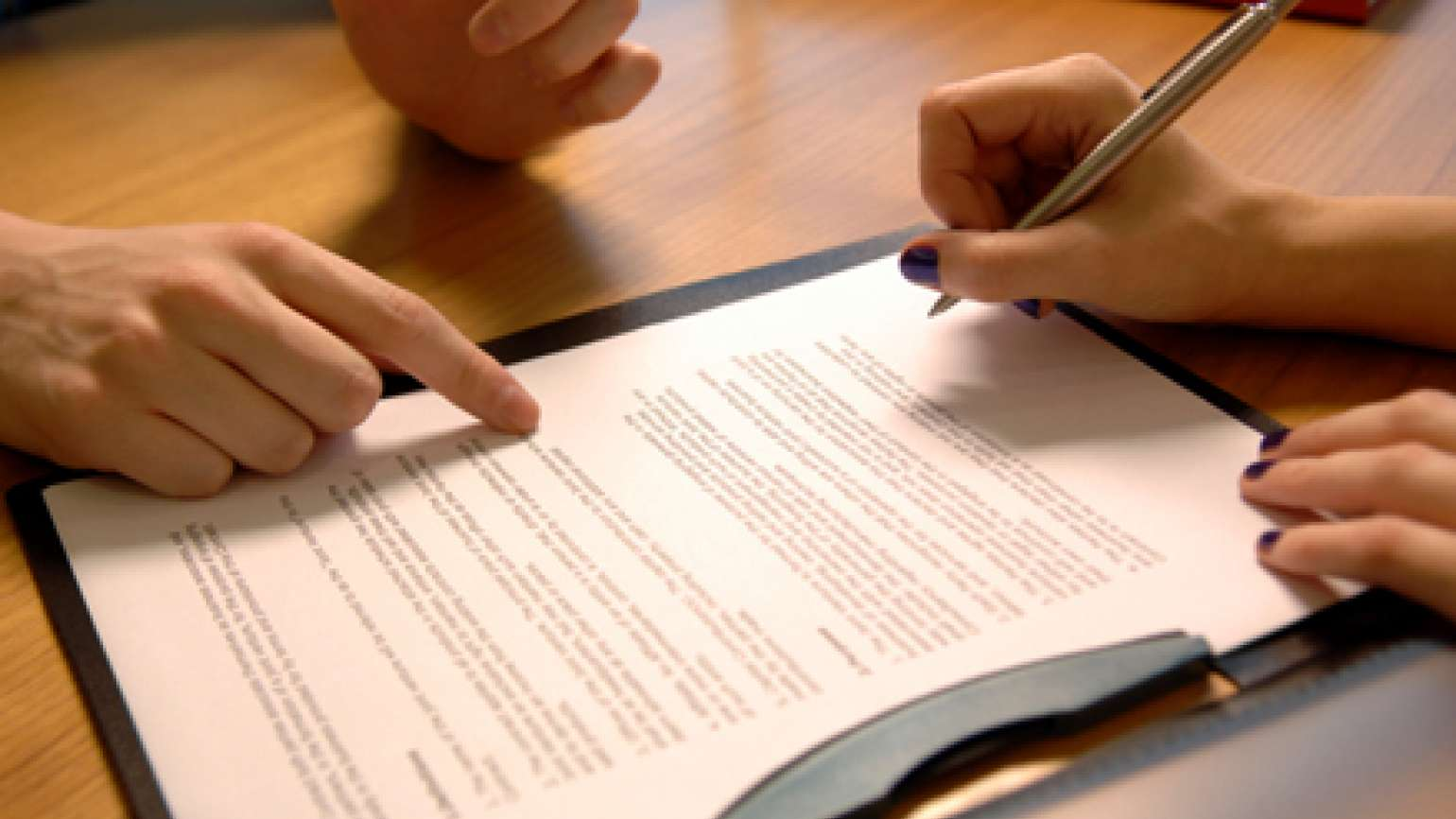 Closeup of woman's hands signing a contract