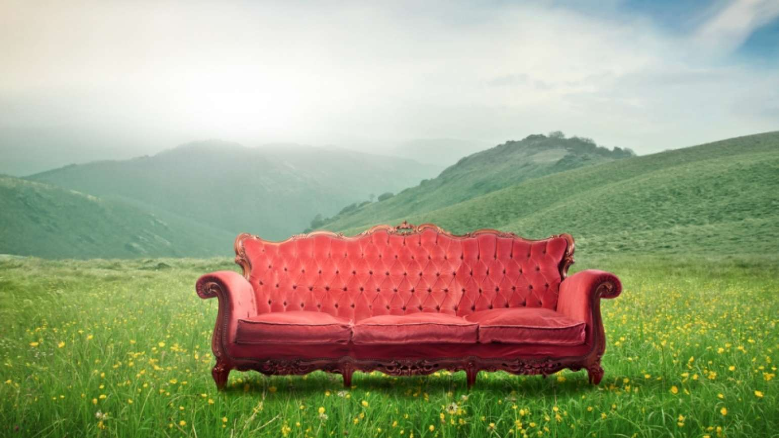 A couch in a beautiful outdoor setting with mountains in the background