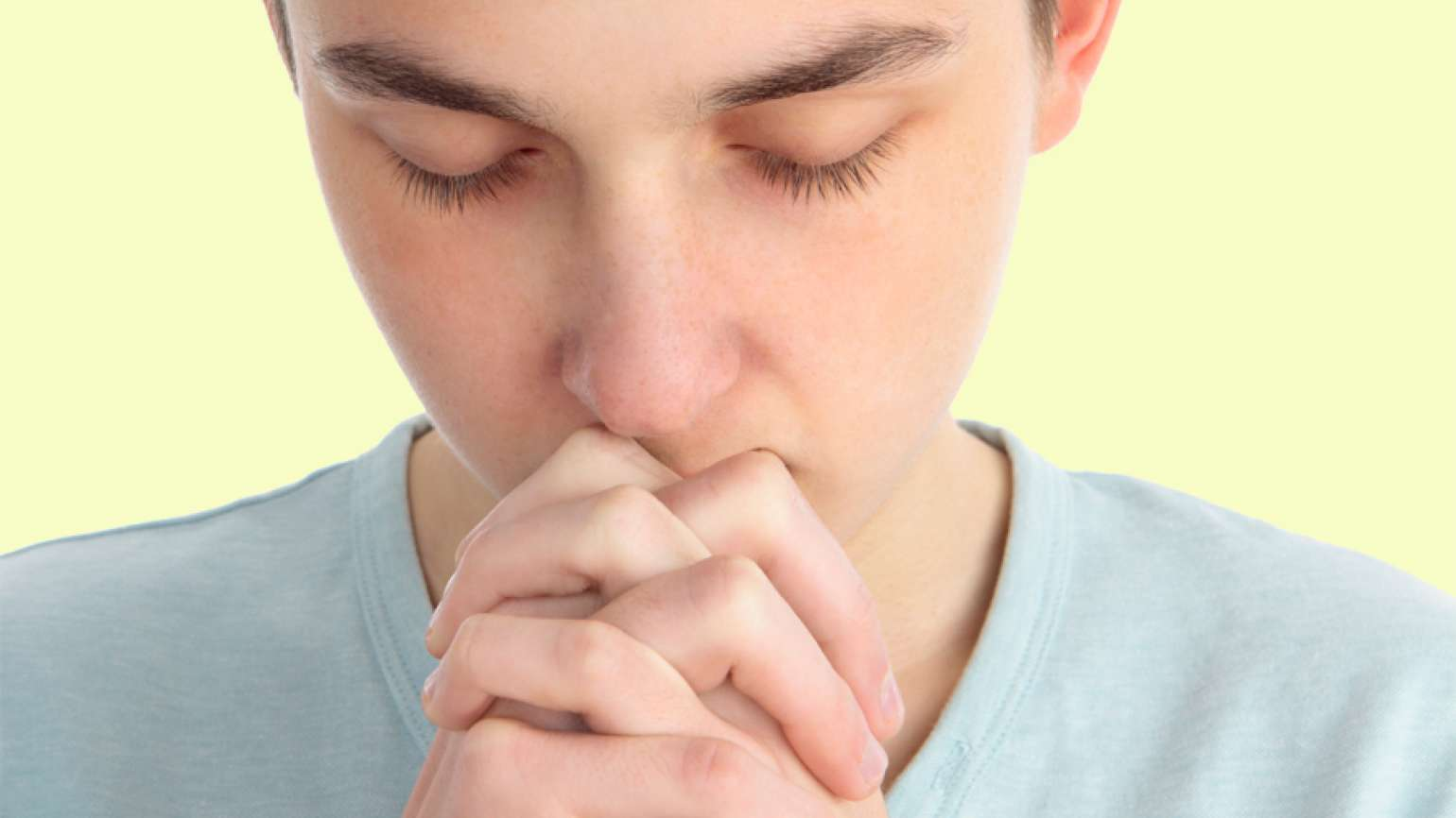 A teenage boy clasps his hands in prayer.