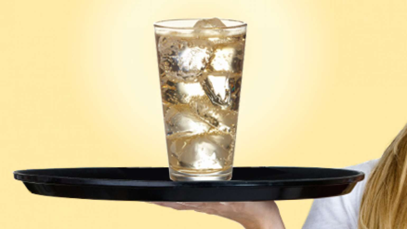 A server's tray with a lone glass of ginger ale on it