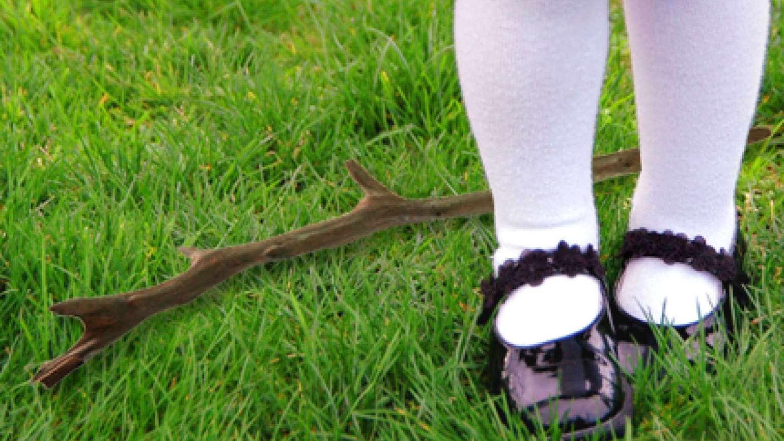 A closeup of a young girl's feet, with a dropped stick lying in the grass