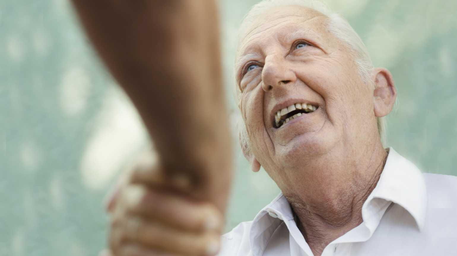 An older man greets his caregiver with a smile and a handshake.