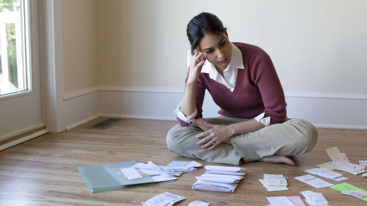 A woman sits on the floor, worried, while surrounded by unpaid bills.