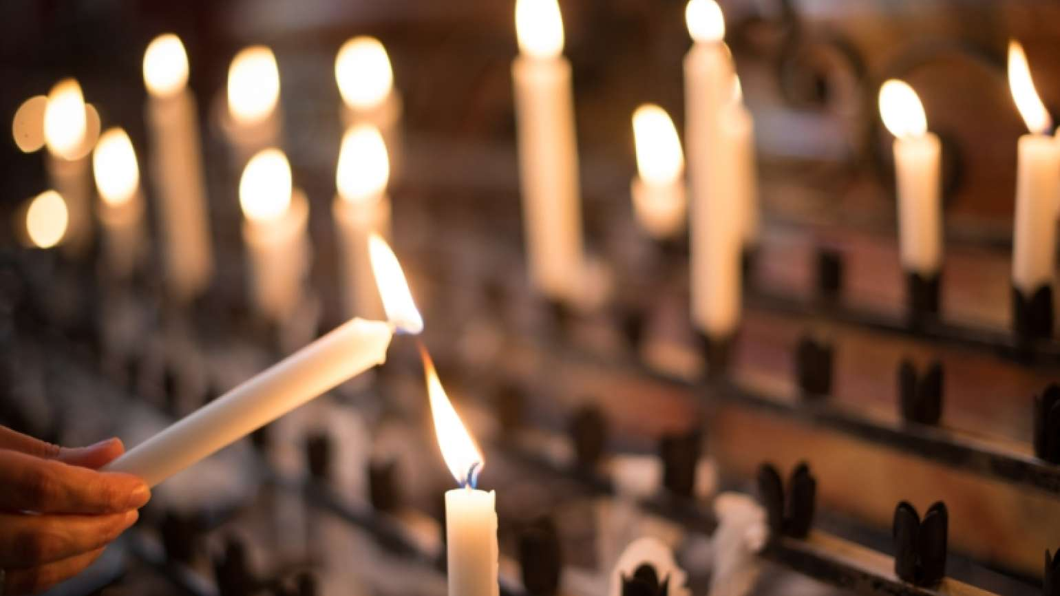 Lighting a candle in church as a gesture of thanksgiving