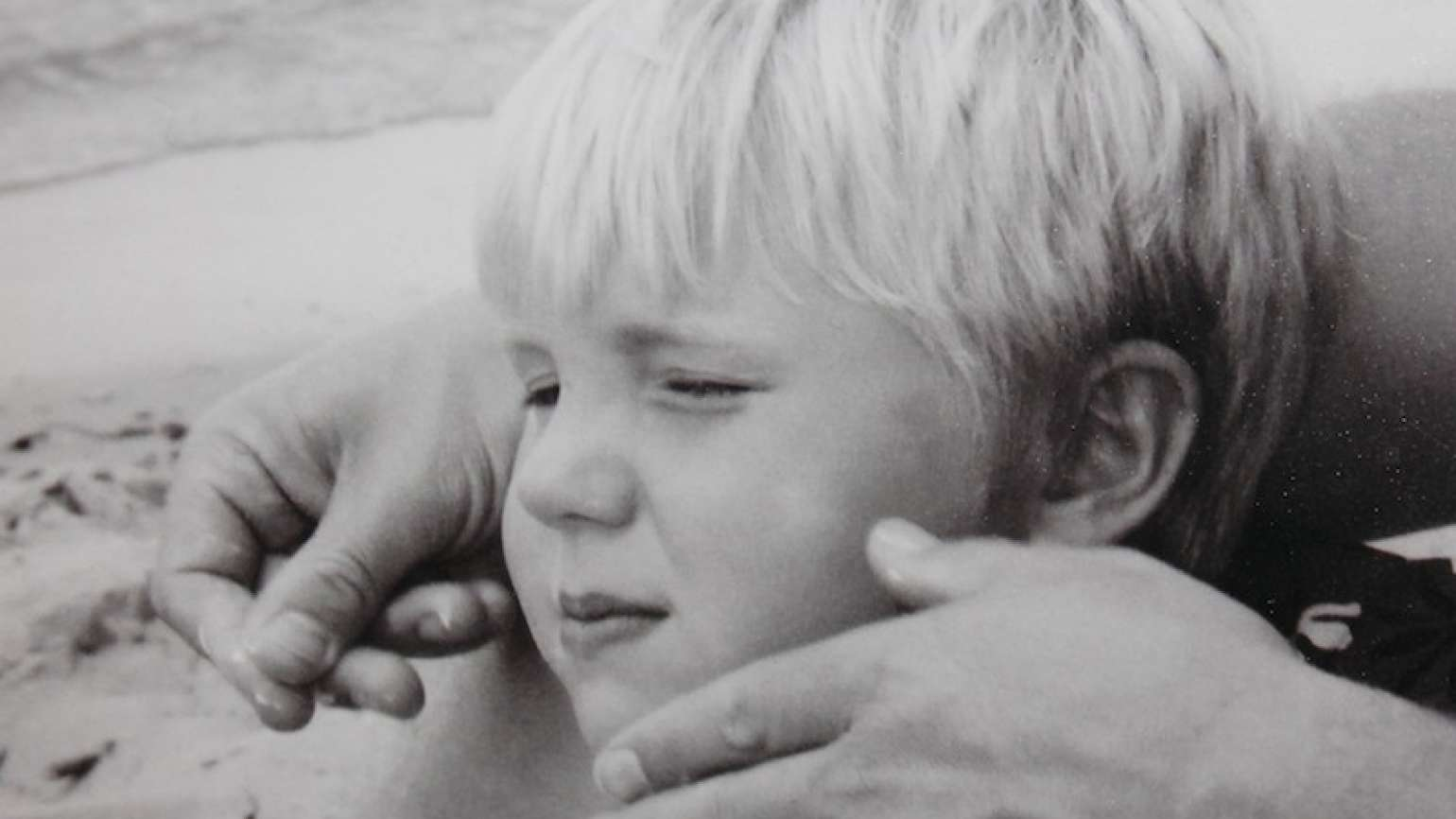Shawnelle's son, Grant, as a young boy, being caressed by his father.