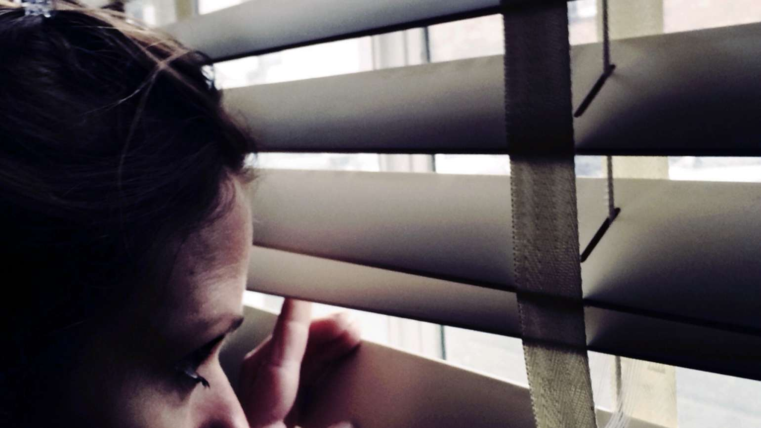 A woman peers anxiously out through her closed blinds.