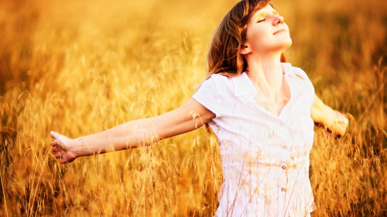 woman with arms outstretched in a field of wheat.
