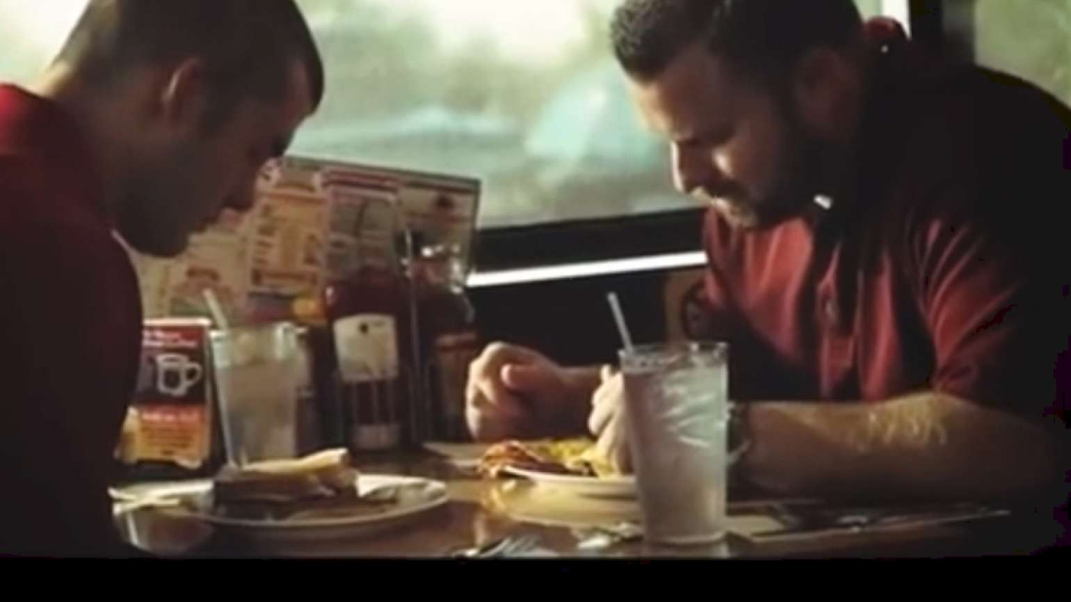 Two men pray over meal.