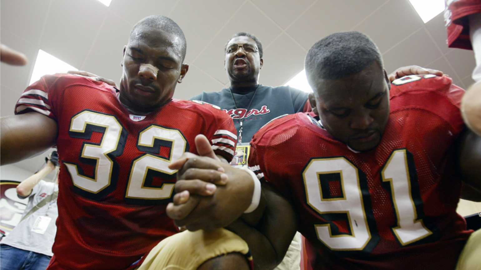 Smith prays with Kevan Barlow (left) and Anthony Adams in the locker room before a game.