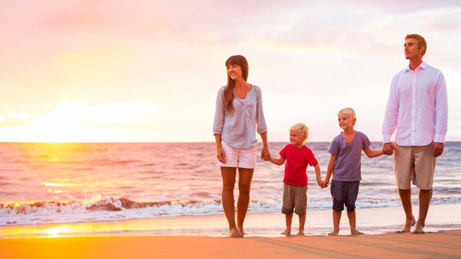 A family of four strolls along the beach as the summer sun sets on the horizon.