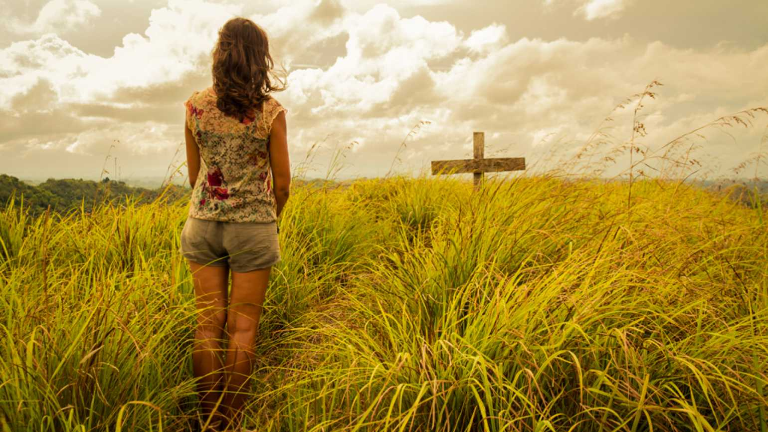 A woman in a field with a cross in front of her