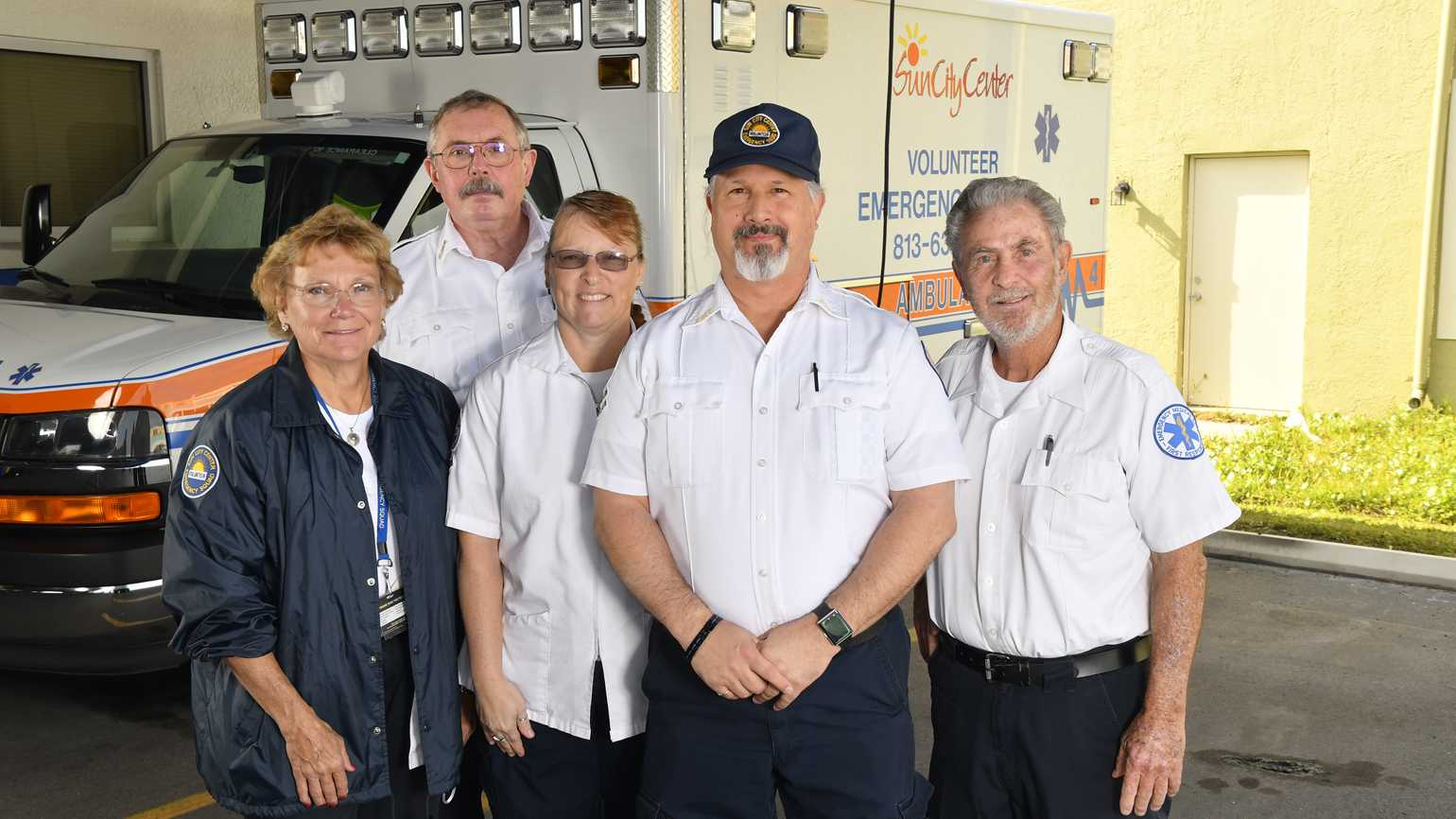 Navarro, Ayers, and Leonard with volunteers standing in front of one of their two ambulances.