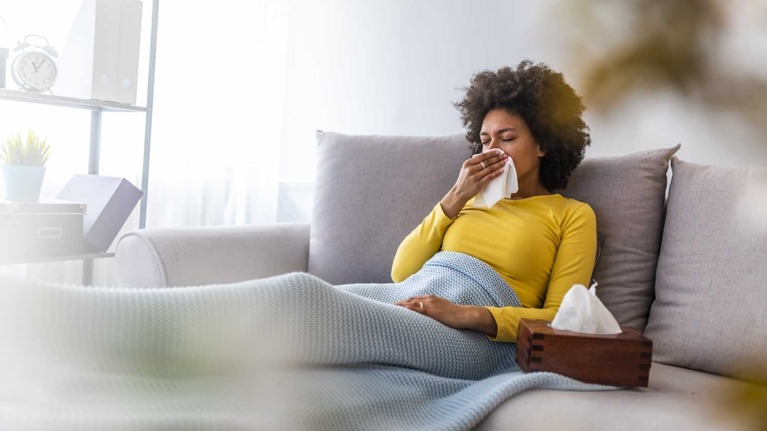 Women with tissue sitting on couch