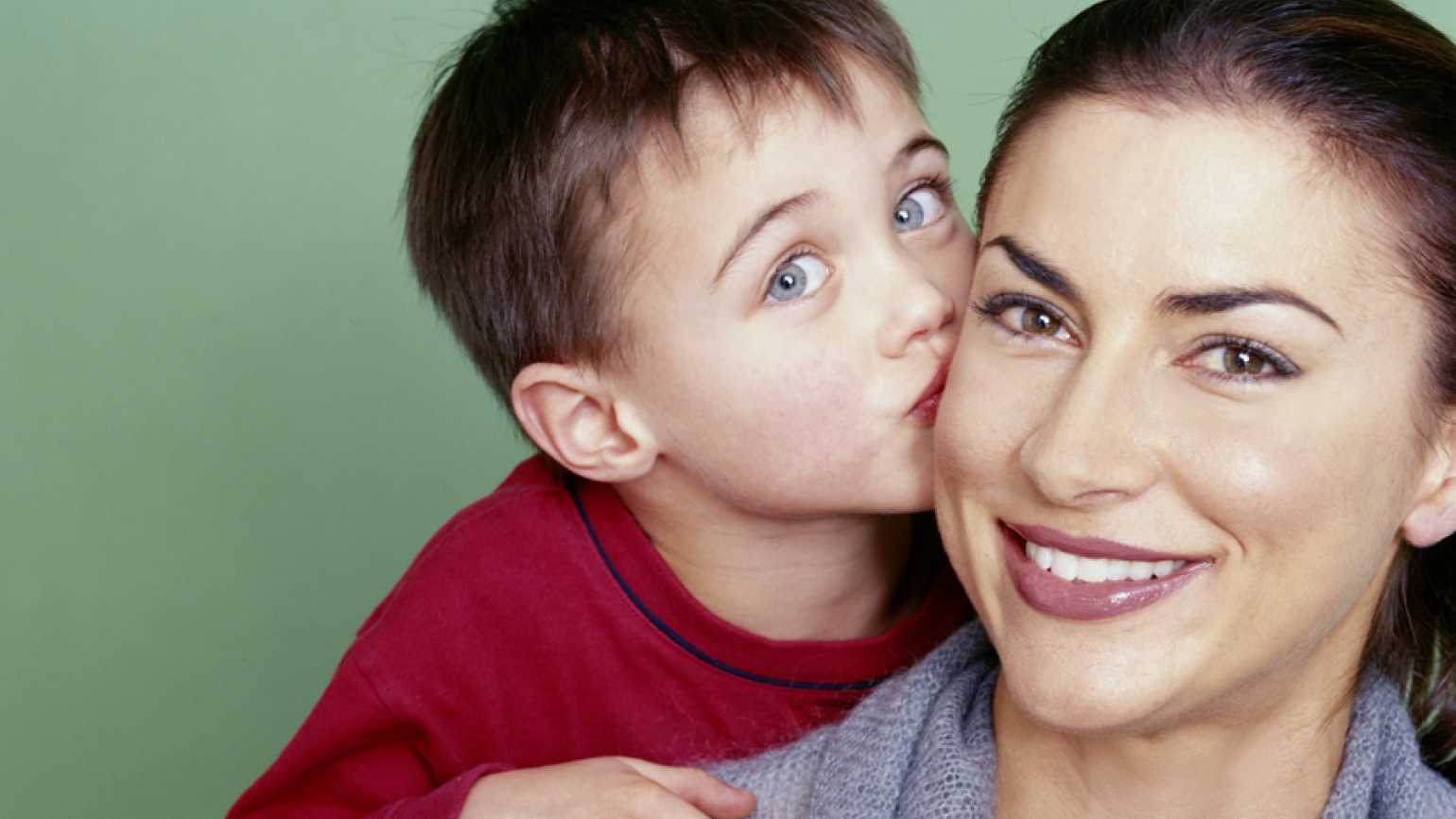 Guideposts: A young boy plants  a smooch on the cheek of his smiling mother