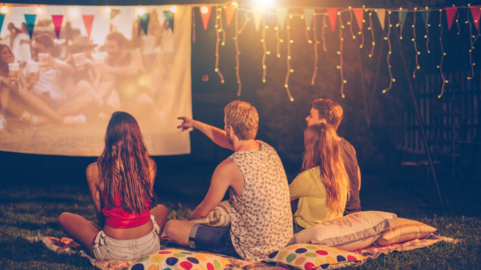 A group of friends watching a movie outdoors during the summer.