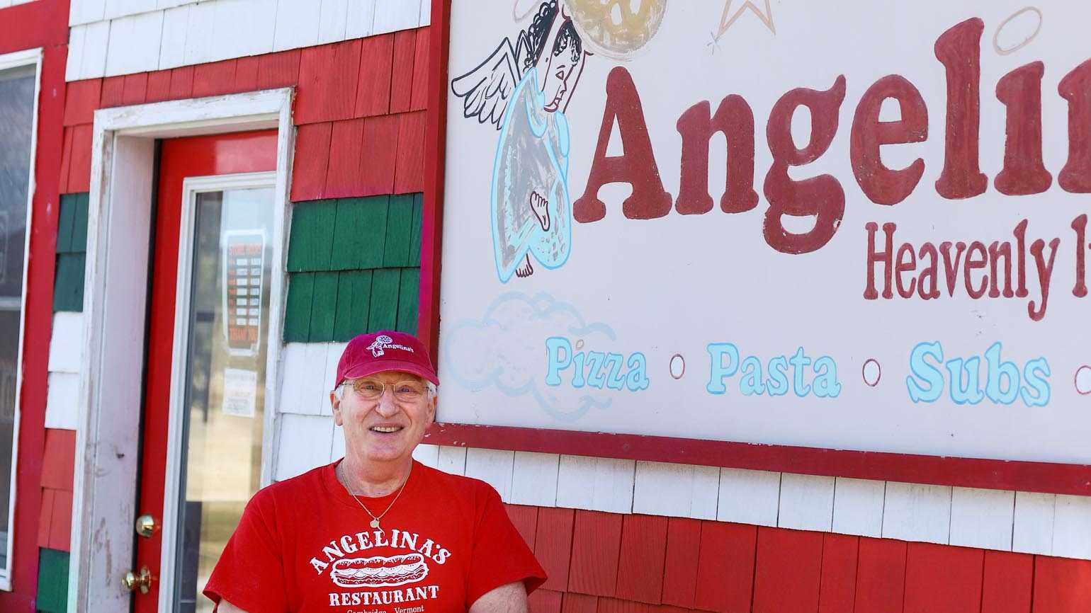 Paul standing by the Angelina sign in front of his business.