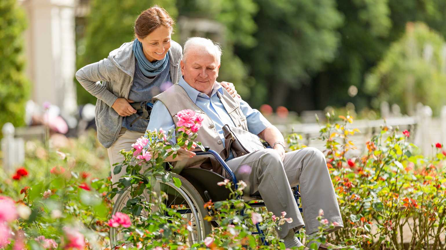 A woman taking her elderly father around the garden.