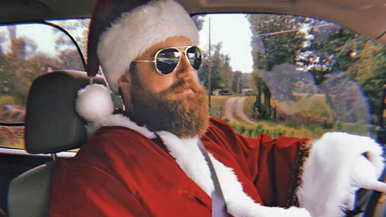Ben Napier behind the wheel dressed in a Santa suit and sunglasses.
