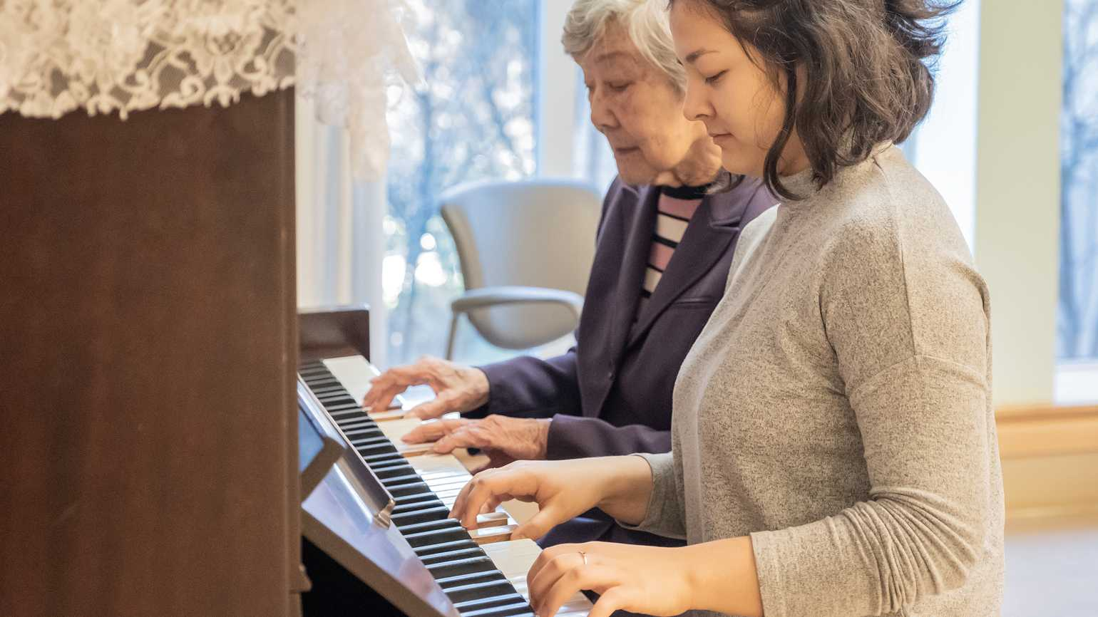 A caregiver plays piano with her client.