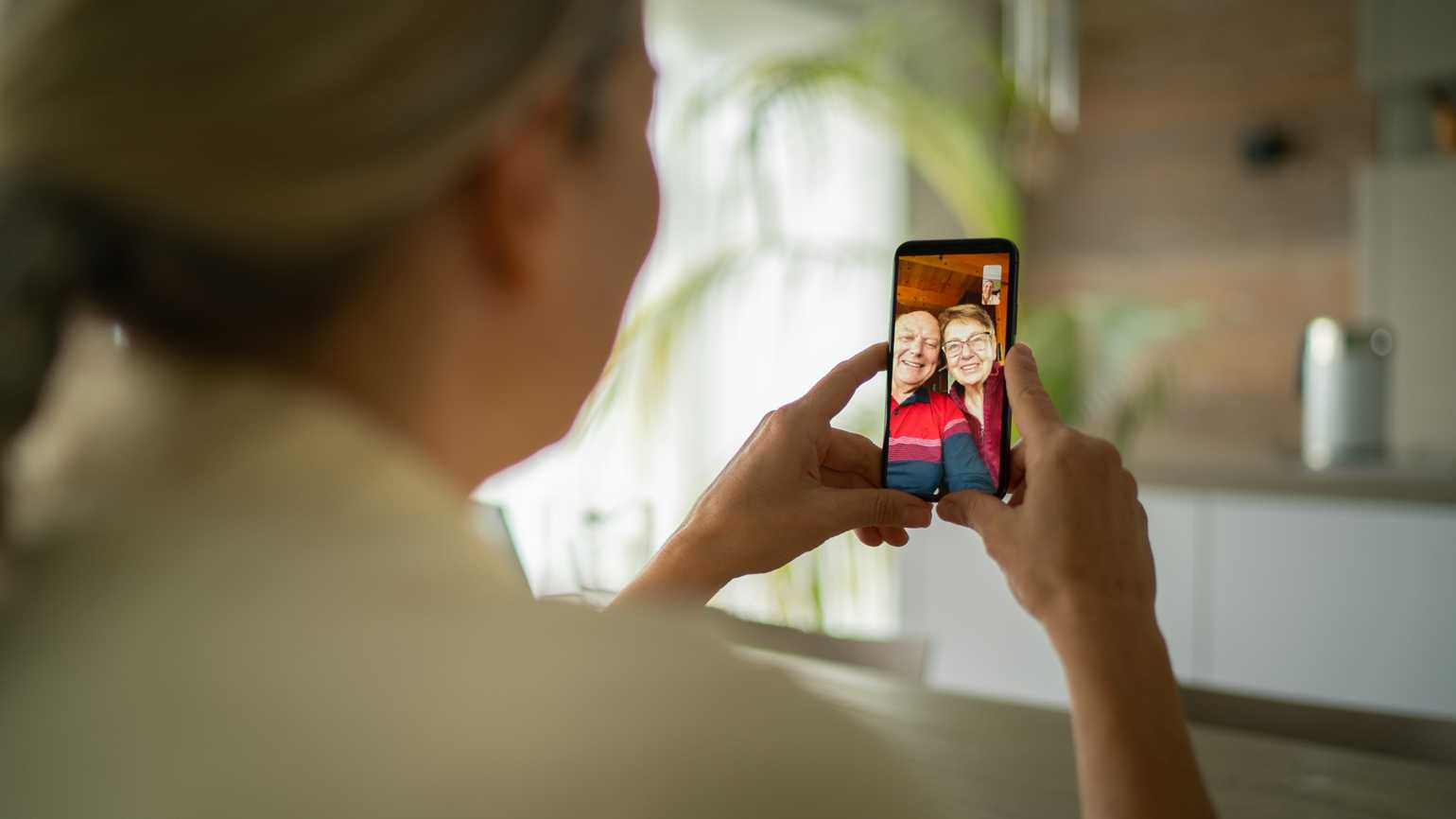 A woman video chatting with her aging parents.