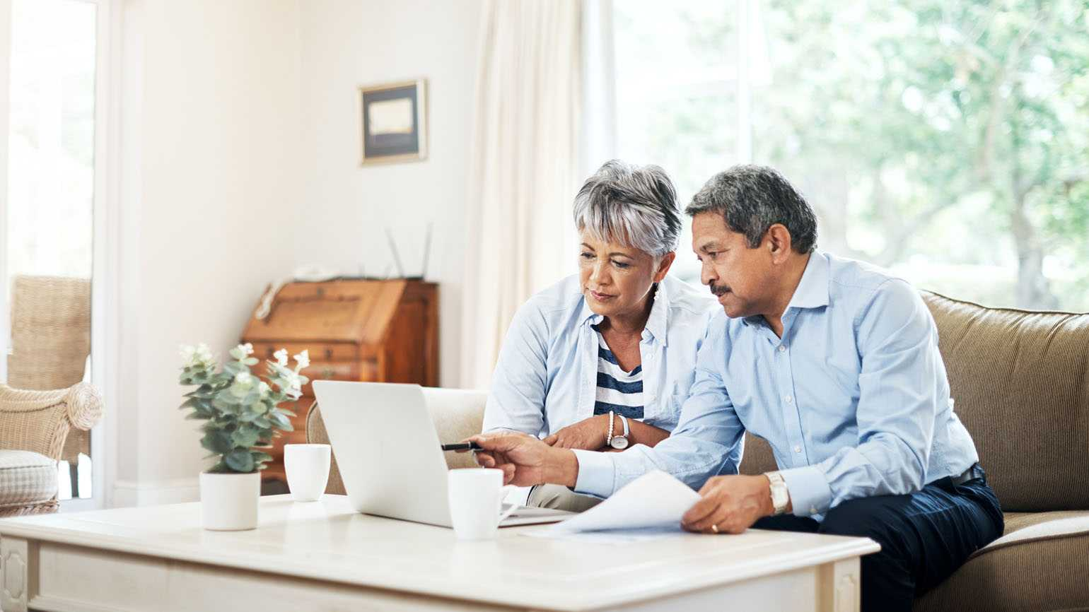 A aging couple planning their finances on a laptop in their home.