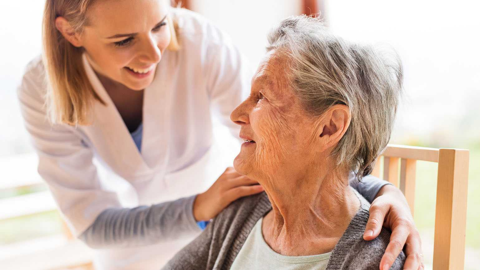 A home care nurse tends to a female senior citizen.