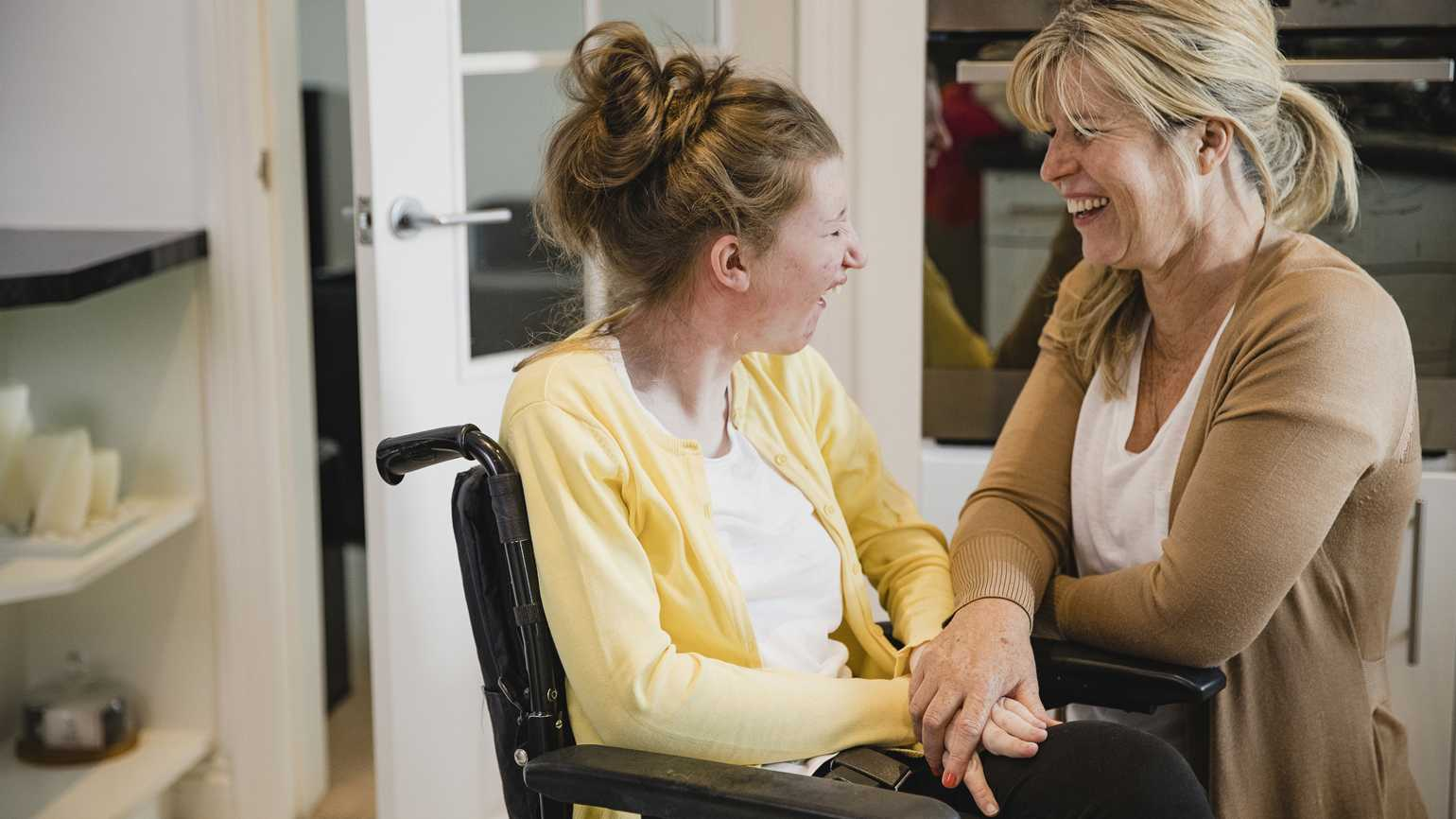 A caregiver parent laughing with her special needs daughter.
