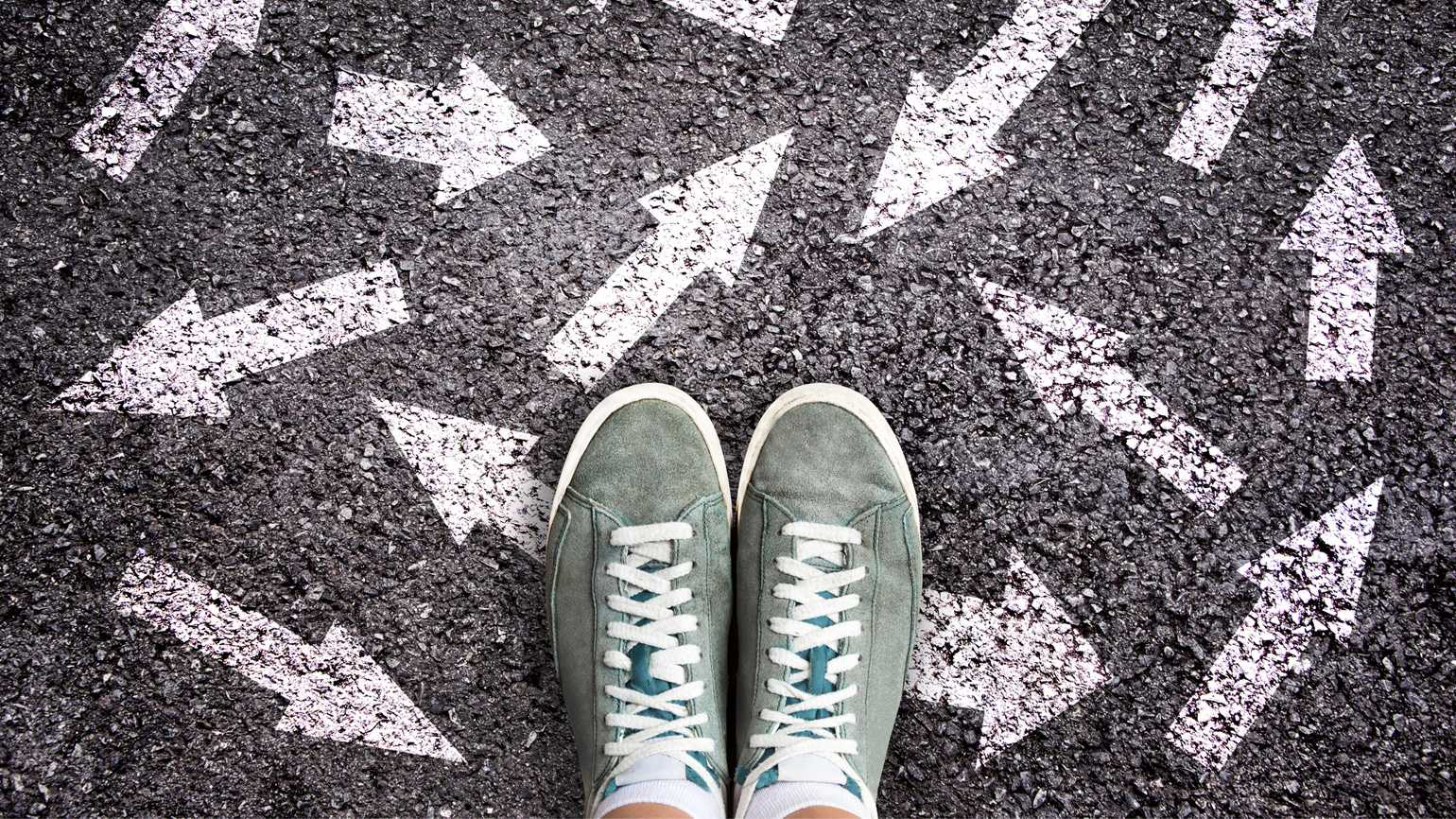 Sneaker shoes and arrows pointing in different directions on asphalt ground.