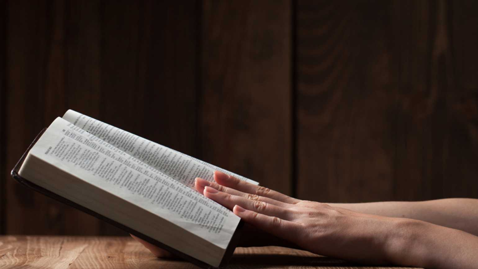 Guideposts: A woman's hand rests on an open Bible.