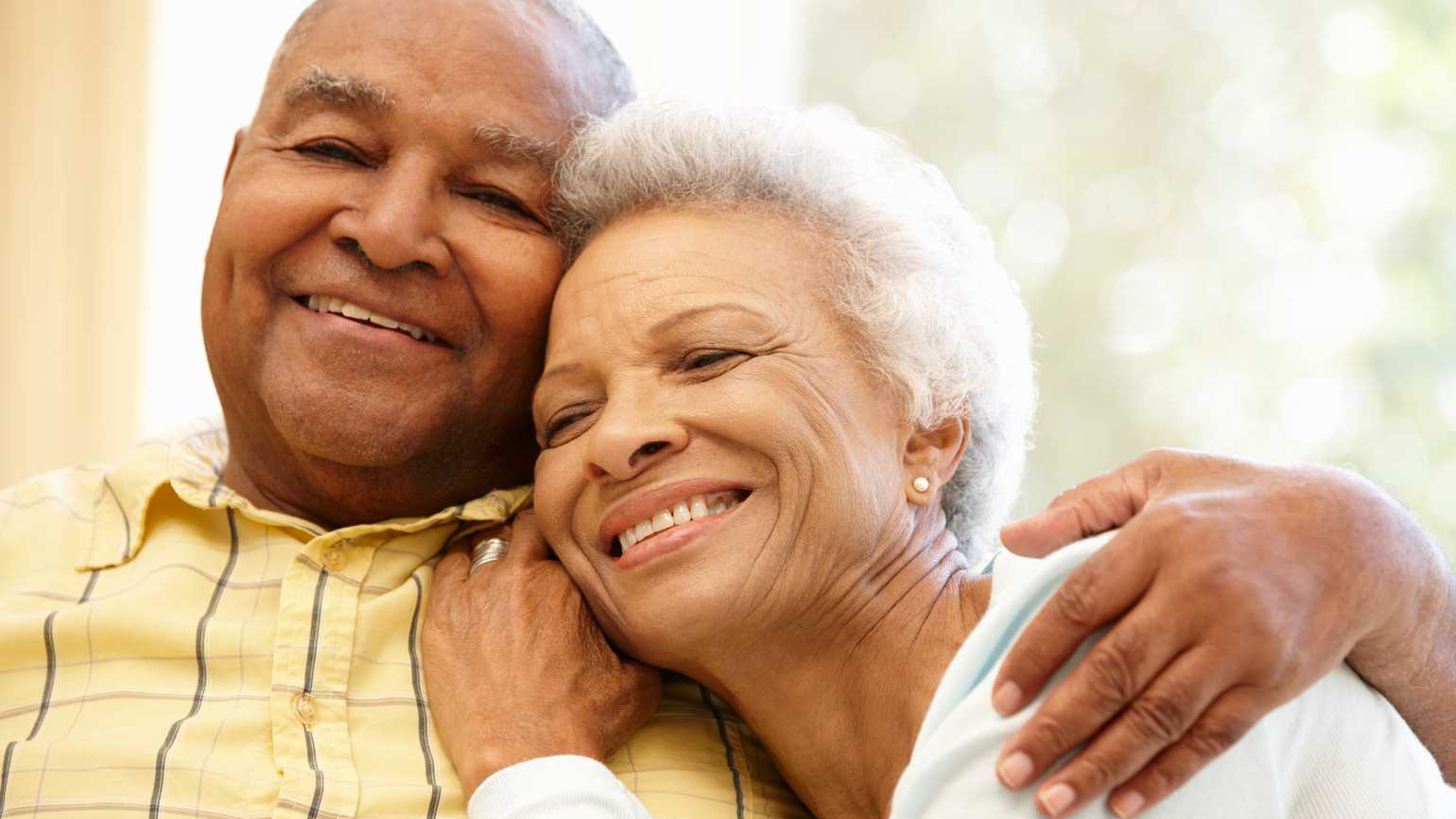 Senior African American couple at home hugging and smiling