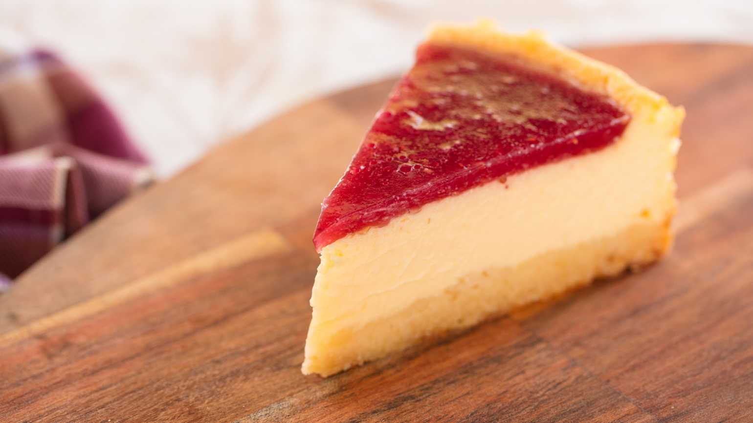 A slice of strawberry cheesecake on a wooden platter.