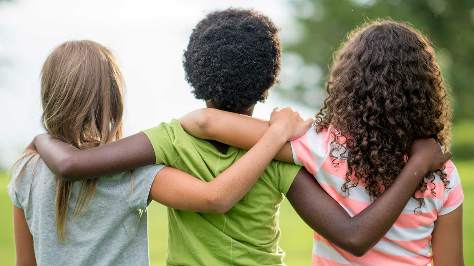 Three children stand, arms draped over one another's shoulders