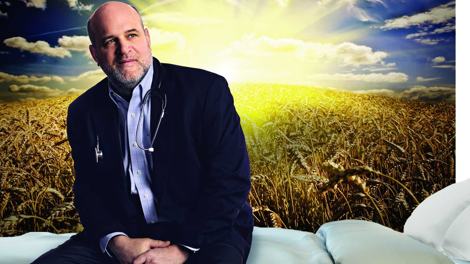 Dr. Christopher Kerr sitting on a bed in front of a brilliant sunrise on wheat plains.