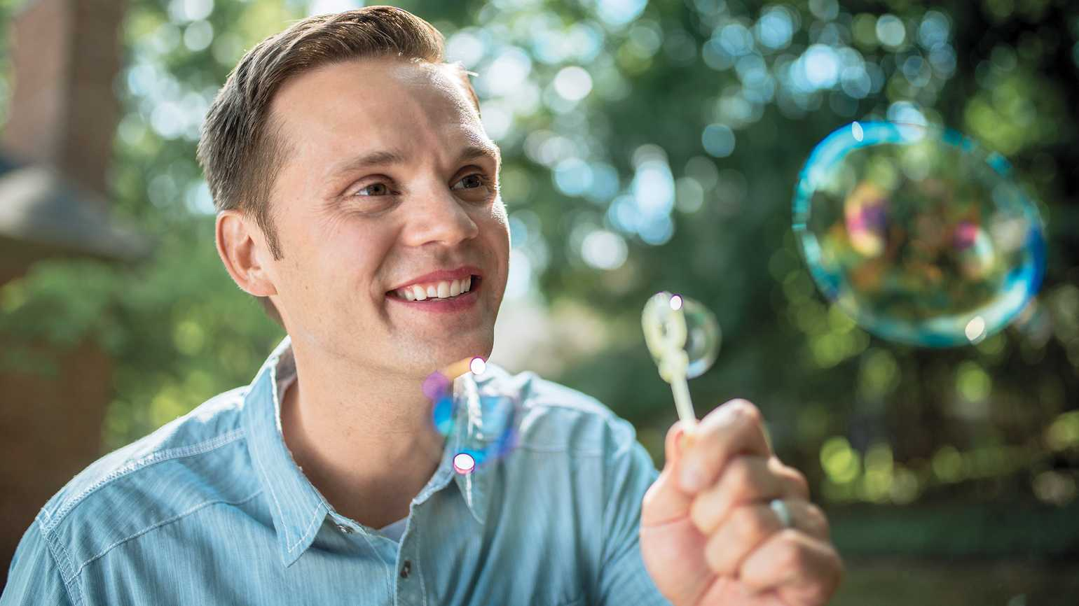 Dr. Anthony T. DeBenedet blowing bubbles outdoors.